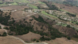 CBAX01_054 - HD stock footage aerial video of fly over mountain range, revealing golf course, homes, Chino Hills, California