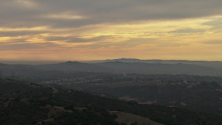 CBAX01_058 - HD stock footage aerial video fly over hills, tilt to neighborhoods, cloudy, Chino Hills, California, sunset