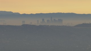 CBAX01_059 - HD stock footage aerial video fly by smoggy skyline beyond hills, Downtown Los Angeles, California, sunset