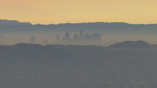 CBAX01_060 - HD stock footage aerial video fly by smoggy skyline beyond hills, Downtown Los Angeles, California, sunset