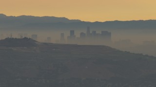 CBAX01_065 - HD stock footage aerial video of a smoggy skyline beyond hills, Downtown Los Angeles, California, sunset