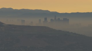 CBAX01_067 - HD stock footage aerial video of a smoggy skyline beyond hills, Downtown Los Angeles, California, sunset