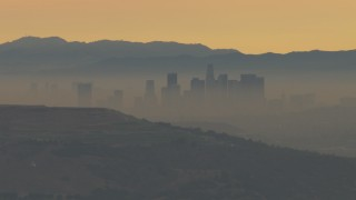 CBAX01_068 - HD stock footage aerial video of smoggy skyline beyond hills, Downtown Los Angeles, California, sunset