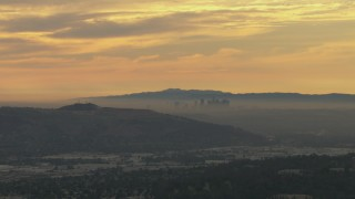 CBAX01_069 - HD stock footage aerial video of smoggy skyline beyond hills, Downtown Los Angeles, California, sunset
