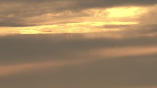 CBAX01_071 - HD stock footage aerial video of sunset-lit clouds, revealing a passenger jet flying by, sunset, Southern California