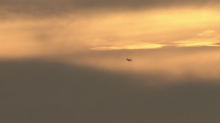 CBAX01_072 - HD stock footage aerial video of a passenger jet cruising by sunset-lit clouds, sunset, Southern California