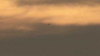 CBAX01_073 - HD stock footage aerial video of a passenger jet cruising by sunset-lit clouds, sunset