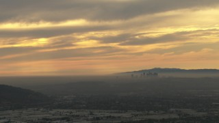 CBAX01_074 - HD stock footage aerial video of a smoggy skyline, cloudy sky, Downtown Los Angeles, California, sunset