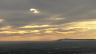 CBAX01_077 - HD aerial stock footage video of the distant skyline, clouds, Downtown Los Angeles, California, sunset