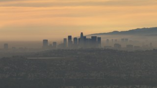 CBAX01_079 - HD stock footage aerial video of flying by smoggy skyline, clouds, Downtown Los Angeles, California, sunset