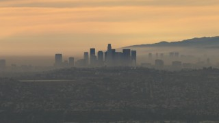 CBAX01_080 - HD stock footage aerial video of flying by smoggy skyline, cloudy, Downtown Los Angeles, California, sunset