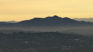CBAX01_090 - HD stock footage aerial video of Hollywood Sign through smog from a distance, Hollywood, California, sunset