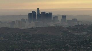 CBAX01_095 - HD stock footage aerial video of a smoggy skyline, hillside neighborhood, Downtown Los Angeles, California, sunset
