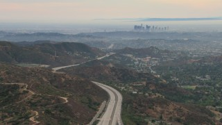 CBAX01_115 - HD stock footage aerial video of a view of hazy downtown from Glendale hills, Downtown Los Angeles, California