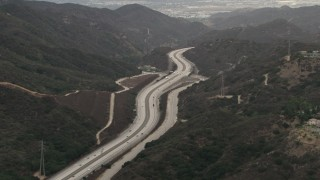 CBAX01_119 - HD stock footage aerial video of flying by Interstate 210, light traffic, Tujunga, California