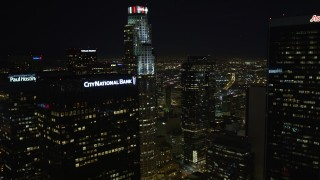 DCA01_025 - 5K stock footage aerial video flying by skyscrapers revealing Los Angeles City Hall at night, California