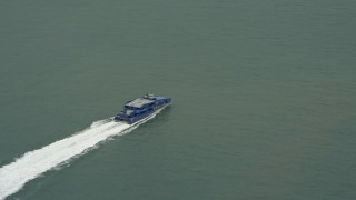 DCA02_011 - 4K stock footage aerial video track a ferry crossing Victoria Harbor, Hong Kong, China