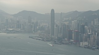 DCA02_015 - 4K stock footage aerial video tilt from a ferry and pan across Hong Kong Island and Victoria Harbor to reveal Kowloon, China