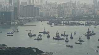 DCA02_016 - 4K stock footage aerial video tilt from ships in Victoria Harbor to reveal Kowloon apartment complexes, Hong Kong, China