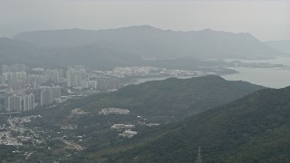 DCA02_025 - 4K stock footage aerial video pan from Tolo Harbor to reveal Tai Po apartment buildings in the New Territories, Hong Kong, China