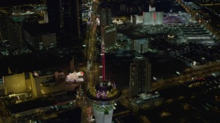 DCA03_084 - 4K stock footage aerial video of orbiting Stratosphere, revealing Las Vegas Boulevard, hotels on Strip, Las Vegas, Nevada Night
