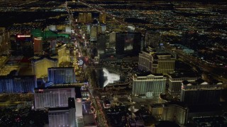 DCA03_129 - 4K stock footage aerial video of hotels along Las Vegas Strip, approaching Paris and Bellagio Fountain water show, Nevada Night