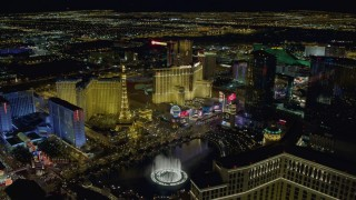 DCA03_194 - 4K stock footage aerial video of flying over Bellagio Fountain toward Paris Hotel and Casino, Las Vegas, Nevada Night