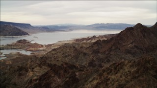 DCA04_082 - 4K stock footage aerial video of flying over rocky ridge in Hiller Mountains, revealing Lake Mead, Nevada