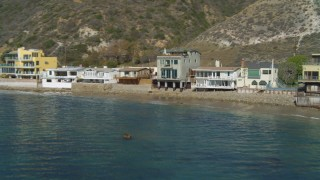 DCA05_102 - 4K stock footage aerial video of flying low over ocean, approaching a beachfront home, Malibu, California