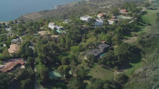 DCA05_109 - 4K stock footage aerial video fly by neighborhood on a cliff, overlooking the Pacific Ocean, Malibu, California