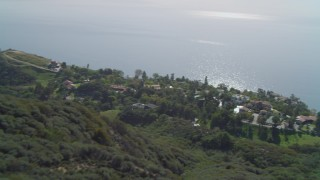 DCA05_110 - 4K stock footage aerial video of hiking trail on hill, homes on cliff overlooking the Pacific Ocean, Malibu, California