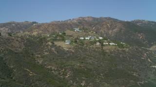 DCA05_112 - 4K stock footage aerial video pan across hills, upscale homes, Malibu, California