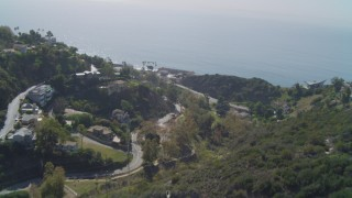DCA05_114 - 4K stock footage aerial video tilt from canyon to reveal coastal neighborhood, coast, ocean, Malibu, California