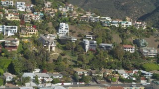 DCA05_115 - 4K stock footage aerial video of flying by hillside homes, focusing on custom home, Malibu, California