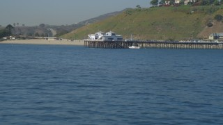 DCA05_119 - 4K stock footage aerial video of flying over small waves in ocean, revealing Malibu Pier, Malibu, California