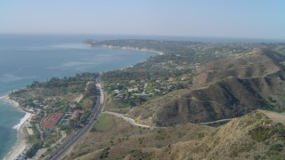 DCA05_125 - 4K stock footage aerial video of flying over a hill, revealing coastal community of Malibu, California