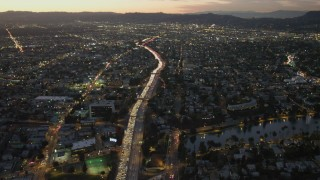 DCA07_030 - 4K stock footage aerial video of following Highway 101 with heavy traffic, Echo Park, California, twilight