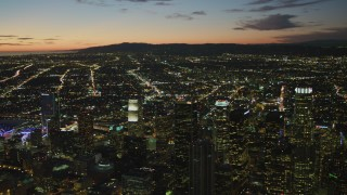 DCA07_051 - 4K stock footage aerial video of flying by Downtown skyscrapers, view of Los Angeles Basin, Santa Monica Mountains, California, twilight