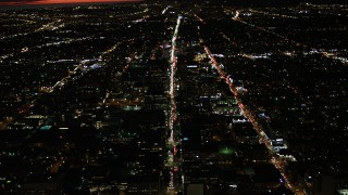 DCA07_066 - 4K stock footage aerial video of following Wilshire Blvd through Koreatown and tilt to a wider view of Los Angeles, California, night