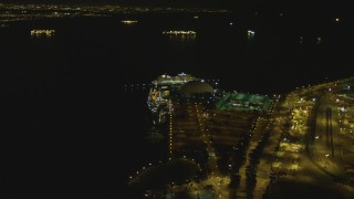 DCA07_126 - 4K stock footage aerial video of RMS Queen Mary, Carnival Cruise Lines building, Port of Long Beach, California, night