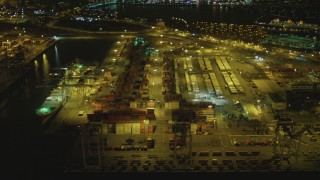 DCA07_129 - 4K stock footage aerial video of flying by cargo cranes, containers, Port of Long Beach, California, night