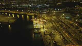 DCA07_132 - 4K stock footage aerial video of flying by cargo ship, cranes, containers, Port of Long Beach, California, night