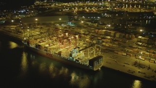 DCA07_133 - 4K stock footage aerial video of flying by a cargo ship, cranes, containers, Port of Long Beach, California, night