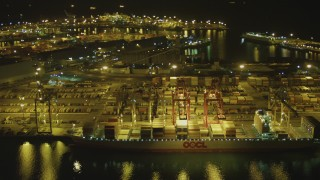 DCA07_134 - 4K stock footage aerial video of flying by cargo ship, cranes, containers, Port of Long Beach, California, night
