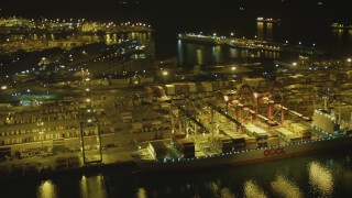 DCA07_135 - 4K stock footage aerial video of flying by cargo ship, cranes, containers, Port of Long Beach, California, night