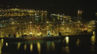 DCA07_136 - 4K stock footage aerial video of approaching cargo ship and cranes at Port of Long Beach, California, night
