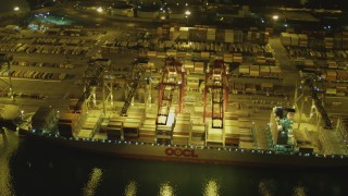 DCA07_137 - 4K stock footage aerial video fly over cargo ship, cranes, containers at Port of Long Beach, California, night