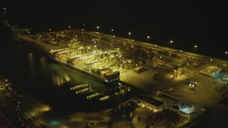 DCA07_141 - 4K stock footage aerial video of approaching cargo ship and cranes, Port of Long Beach, California, night
