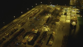 DCA07_144 - 4K stock footage aerial video pan across cargo containers, reveal cargo ship, cranes, Port of Long Beach, California, night