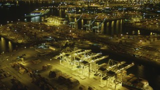 DCA07_145 - 4K stock footage aerial video tilt from cargo ship to wider view of Port of Long Beach, California, night